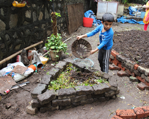 Children work on similar smaller pits that are gardens-in-the-making