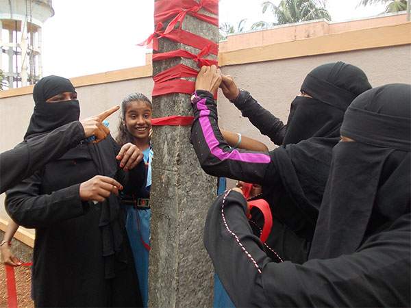 Women tying a red ribbon to an electric pole outside their gram panchayat's office as a symbol of the issues to be resolved.